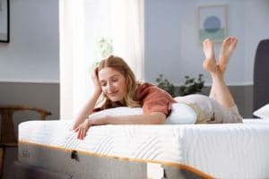Nainen makaamassa sängyllä