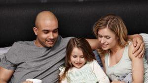 Perhe lukemassa kirjaa sängyssä