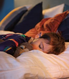 Lapsi nukkumassa unilelun kanssa